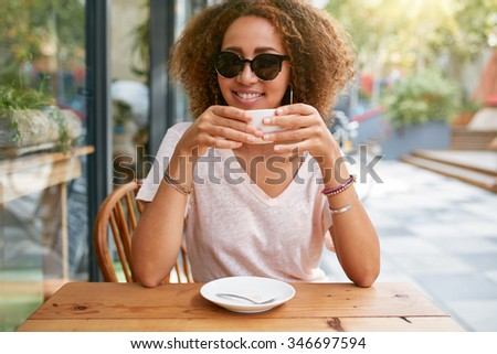 Portrait of pretty young girl drinking coffee. African young woman holding a cup of coffee looking at camera smiling while sitting outdoors in a sidewalk cafe. - stock photo