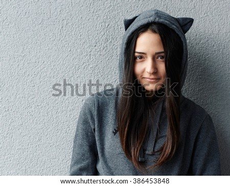 Portrait of pretty young girl in grey hoodie smiling at camera against of textured wall. - stock photo
