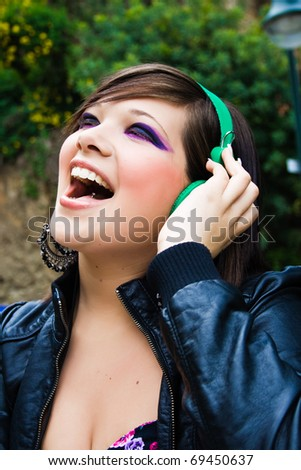 portrait of pretty young girl listening music with enthusiasm