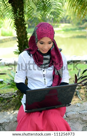Portrait of pretty young girl smile while working on laptop