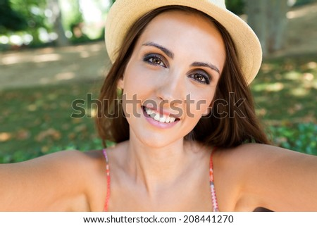 Portrait of pretty young girl taking selfies with her smart phone in the garden. - stock photo