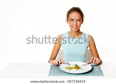 Portrait of pretty young girl with fork and knife in hands and plate with pea starter in front - stock photo
