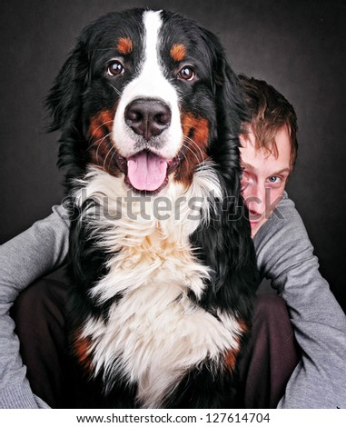 Portrait of Pretty young, happy, man with  beautiful Bernese mountain dog (Berner Sennenhund) - stock photo