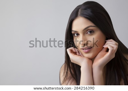Portrait of pretty young Indian woman with long hair isolated over colored background - stock photo