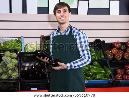 Portrait of pretty  young male posing in grocery and smiling