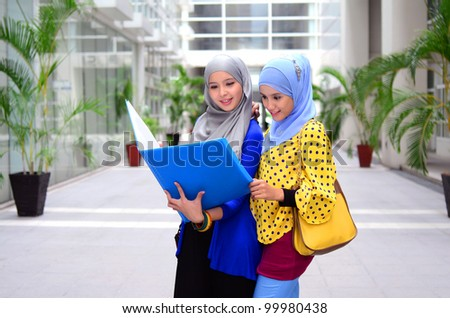 Portrait of pretty young Muslim woman sharing idea while hold file and smile - stock photo