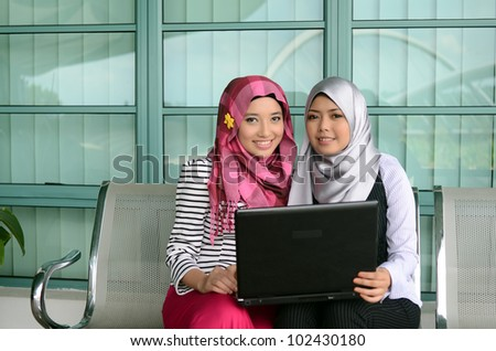 Portrait of pretty young Muslim woman sharing idea while hold notebook and smile - stock photo