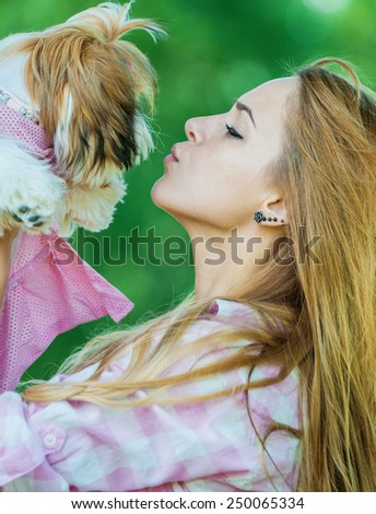 Portrait of pretty, young, smiling woman holding small fluffy dog, against background of summer green park - stock photo
