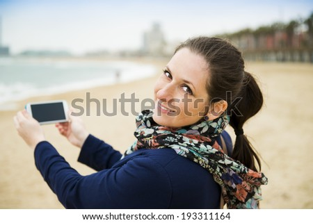 Portrait of pretty young traveler taking picture with cell phone on the beach on a cold day. - stock photo