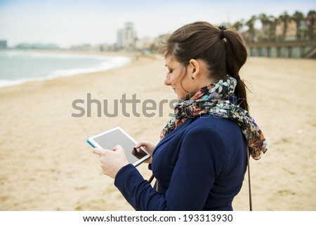 Portrait of pretty young traveler with digital tablet on the beach on a cold day. - stock photo