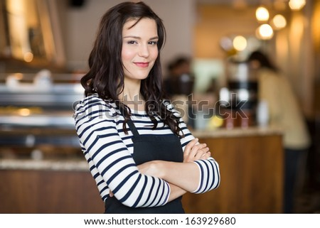 Portrait of pretty young waitress standing arms crossed in cafeteria - stock photo