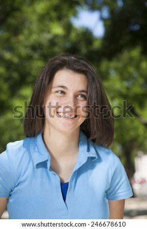 portrait of pretty young woman face with blue shirt laughing and green trees background