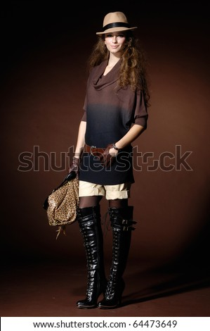 Portrait of pretty young Woman holding handbag In Studio