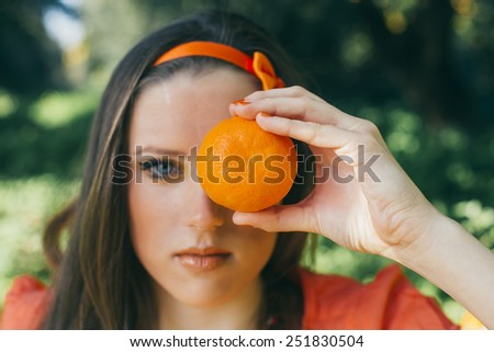 Portrait of pretty young woman holding  orange at summer green park. - stock photo