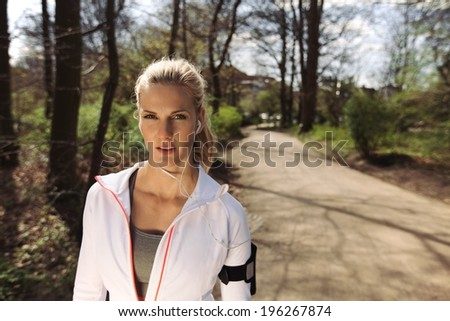 Portrait of pretty young woman in sports clothing wearing earphones while on fitness routine in forest. Young female runner of forest trail. - stock photo