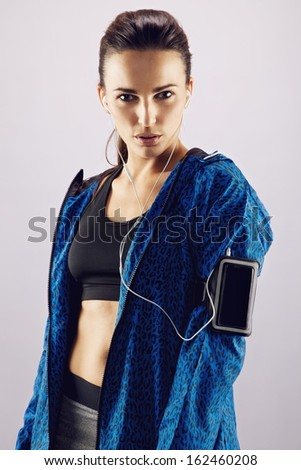 Portrait of pretty young woman in sportswear listening to music with mobile phone on armband. Beautiful young female athlete standing against grey background - stock photo