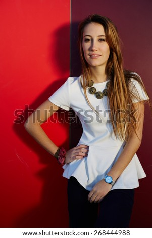 Portrait of pretty young woman posing on colored wall background while looking away, stylish teenager girl posing on bright background - stock photo