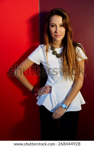 Portrait of pretty young woman posing on colored wall background while looking to the camera, stylish teenager girl posing on bright background - stock photo