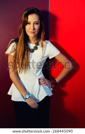 Portrait of pretty young woman posing on colored wall background while looking to the camera, stylish teenager girl posing on bright background, filtered image - stock photo
