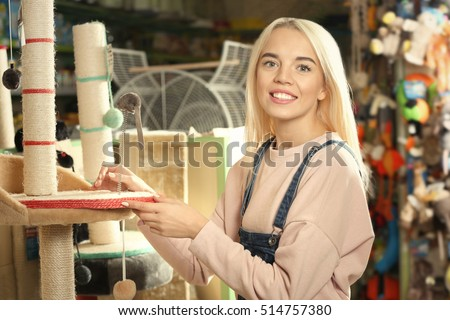 Portrait of pretty young woman selecting cat scratching post in pet shop