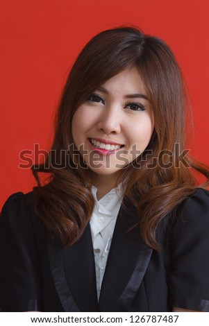 Portrait of pretty young woman smiling against red background