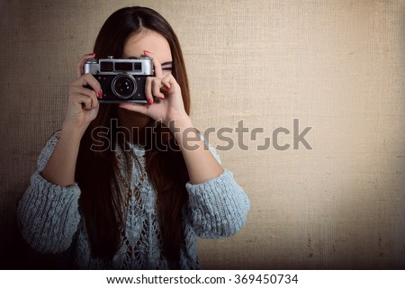 Portrait of pretty young woman taking photo with retro noname soviet photo camera. Photographer getting pictures in hipster style indoor over canvas background. Image toned. - stock photo