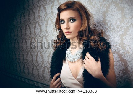 Portrait of pretty young woman with beads and furs