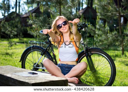 Portrait of pretty young woman with bicycle in a park smiling with thumbs up gesture - Outdoor - stock photo