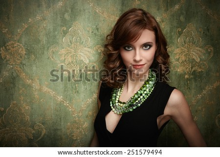 Portrait of pretty young woman with green beads - stock photo