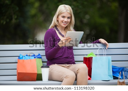 Portrait of pretty young woman with shopping bags using tablet PC on park bench - stock photo