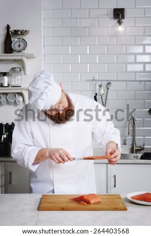 Portrait of professional and experienced chef cook in uniform diligently cutting salmon fish on fillets with knife on a board, male chef preparing gourmet meal of seafood in modern kitchen - stock photo