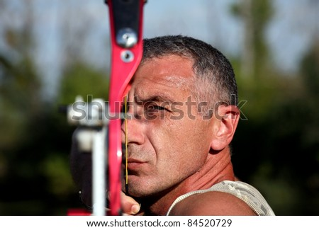 Portrait of professional bowman aiming with bow and arrow , horizontal - stock photo