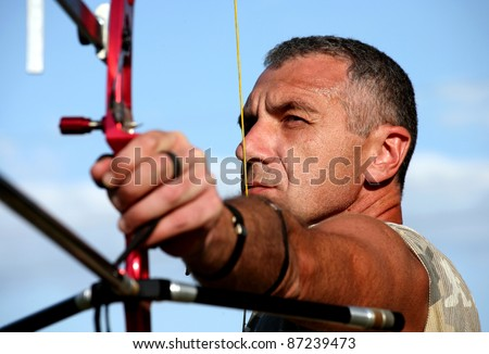 Portrait of professional bowman aiming with bow and arrow , horizontal