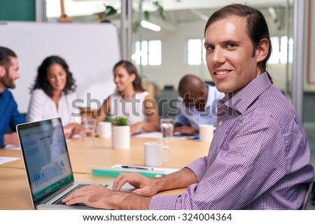 portrait of professional business man during coworkers boardroom meeting with laptop computer taking notes - stock photo