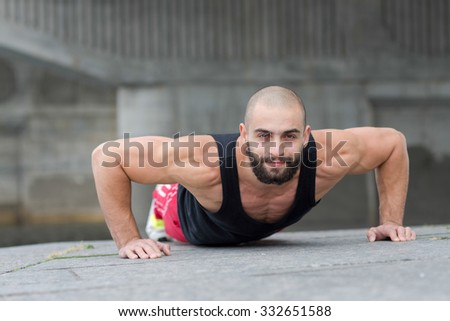 Portrait of professional fitness athlete trainer. Muscular male sportsman is training himself. Outdoors fitness sport concept. Intensive street pushups workout