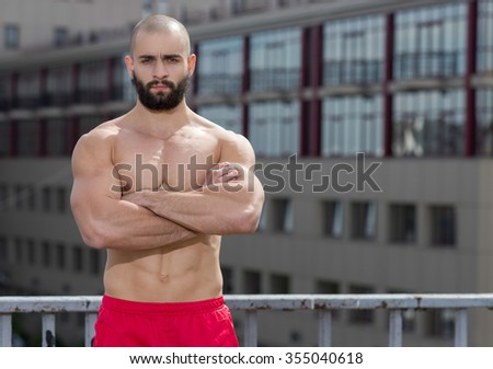 Portrait of professional fitness athlete trainer. Muscular male sportsman is training himself. Outdoors fitness sport concept. Intensive street workout - stock photo