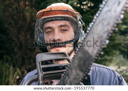 Portrait of professional gardener with chainsaw. - stock photo