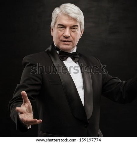 Portrait of professional hypnotist on black background - stock photo
