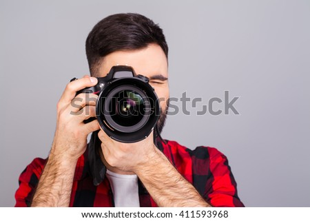 Portrait of  professional photographer with digital camera taking photos - stock photo