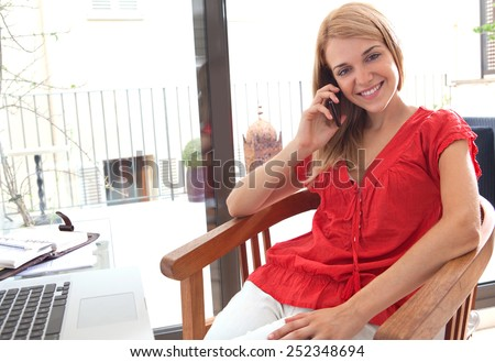 Portrait of professional woman sitting smiling in home office space using a smartphone mobile phone to have a call conversation. Student using a laptop computer. Lifestyle and technology, interior. - stock photo