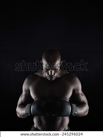 Portrait of professional young male boxer looking down on black background. African boxer preparing for fight. - stock photo