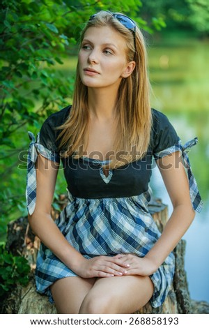 Portrait of profile young beautiful woman against summer garden.