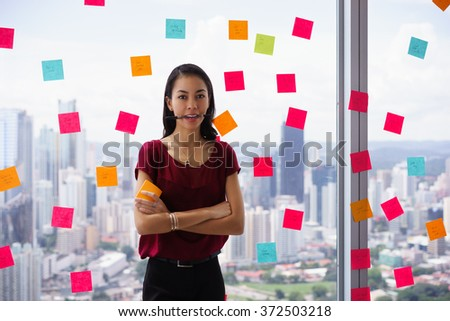 Portrait of proud assistant with pen in mouth. The woman stands in office at high floor, against window full of adhesive notes with tasks - stock photo
