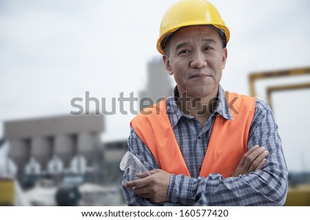 Portrait of proud worker with arms crossed in protective workwear