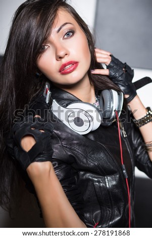 Portrait of provocative young brunette posing with headphones - stock photo