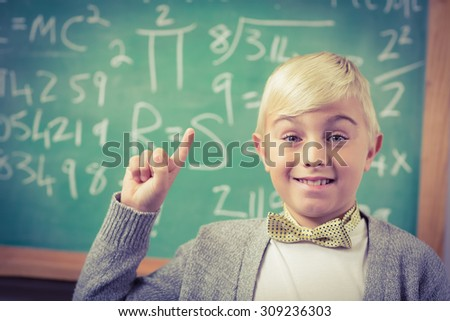 Portrait of pupil dressed up as teacher having an idea in front of chalkboard