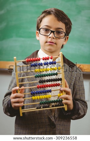 Portrait of pupil dressed up as teacher holding abacus in a classroom - stock photo
