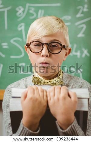 Portrait of pupil dressed up as teacher holding books in a classroom - stock photo