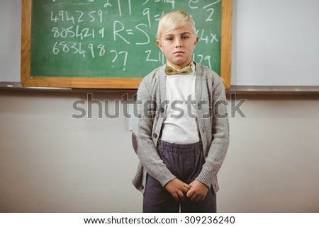 Portrait of pupil dressed up as teacher in front of chalkboard in a classroom - stock photo