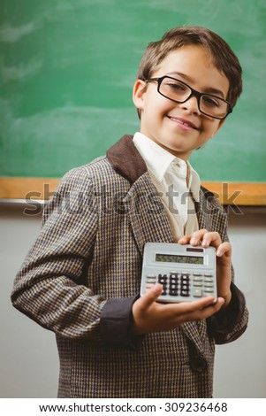 Portrait of pupil dressed up as teacher showing calculator in a classroom - stock photo